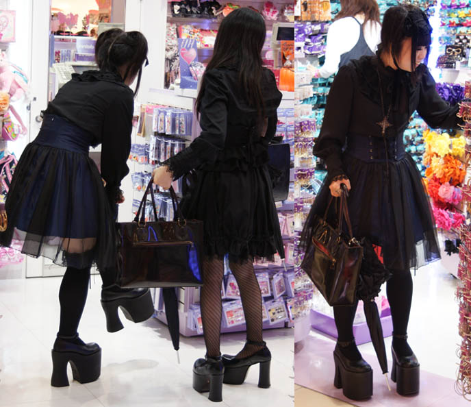 Harajuku girls in Gothic Lolita kurololi dresses. Big platform doll shoes, black veils and corset dresses, crucifix necklace and fishnet tights on Goth teen girls in Tokyo Japan.