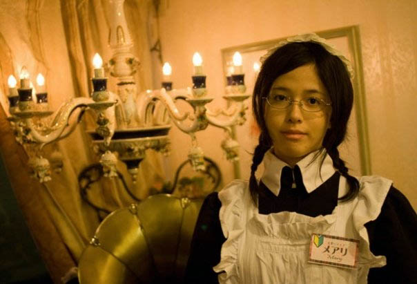 Maid in meido cafe, cosplay costume in Tokyo, Japan. Candles, Victorian maid outfit worn by Japanese girl with pigtails and glasses. Akina, Gothic Lolita fashion designer Lang Leav from Australia.